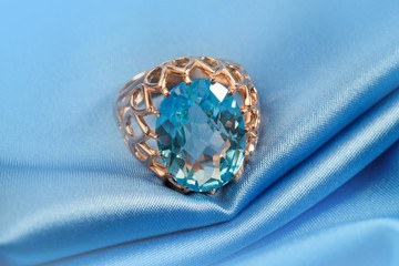 Golden jewelry ring with blue topaz