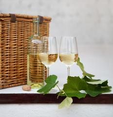 Still life with glasses of white wine, bottle, basket