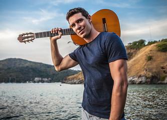 Handsome smiling man pose near evening beach with guitar.