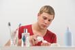 Young man shaving at home