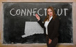 Teacher showing map of connecticut on blackboard