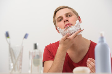 Closeup portrait of young man applying shaving cream