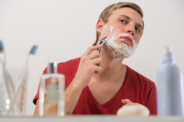 Young man shaving at home