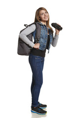 Girl with backpack and binoculars in full length