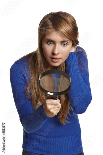 Astonished girl looking through the magnifying glass downwards