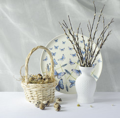 Quail eggs in a basket and willow branches