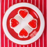 cheesecakes in  heart on a striped tablecloth. top view
