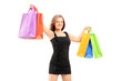Young smiling woman in black dress holding shopping bags