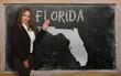 Teacher showing map of florida on blackboard