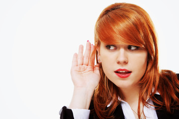 Business woman with hand to ear listening isolated