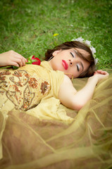 SLEEPING BEAUTY lying on the forrest with a rose