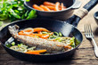 Closeup of freshly fried fish with lemon and carrots