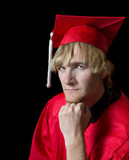 Handsome high school graduate wearing red cap and gown