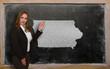Teacher showing map of iowa on blackboard