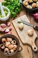 Closeup of preparing baked snails with garlic butter