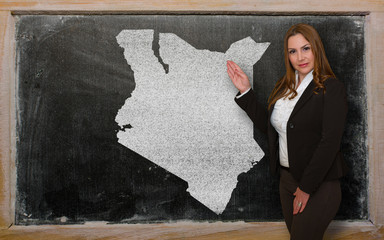 Teacher showing map of kenya on blackboard