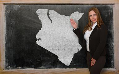 Teacher showing map of kenya on blackboard