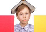 Little blond boy with a book on his head looking tired from behi