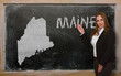 Teacher showing map of maine on blackboard