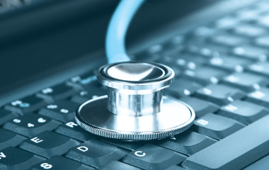 Computer concept of a stethoscope closeup on a computer keyboard