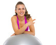 Smiling fitness woman with fitness ball pointing on copy space