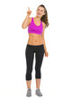 Full length portrait of fitness woman pointing on copy space
