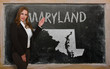 Teacher showing map of maryland on blackboard