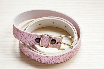 pink women style belt on a light wooden background