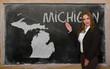 Teacher showing map of michigan on blackboard