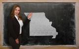 Teacher showing map of missouri on blackboard