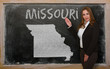 Teacher showing map of missouri on blackboard