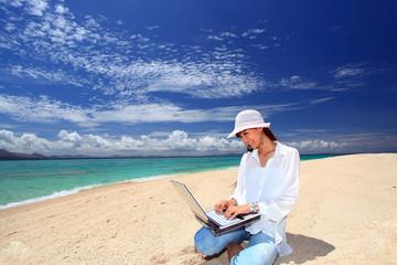 海辺でパソコンを楽しむ女性