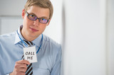 "Handsome businessman showing ""call me"" text on a badge"