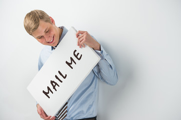 "Handsome businessman showing ""mail me"" text on a billboard"