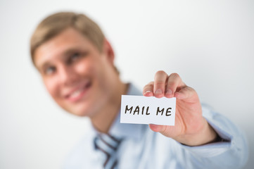 """Handsome businessman showing """"mail me"""" text on a business card"""