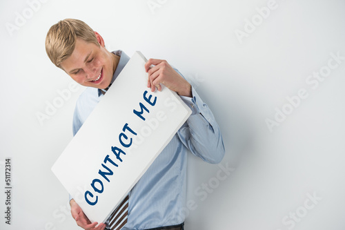 "Handsome businessman showing ""contact me"" text on a billboard"