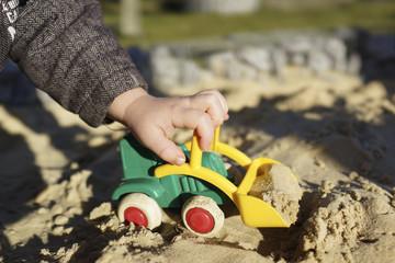 Spielen im Sandkasten mit Bagger