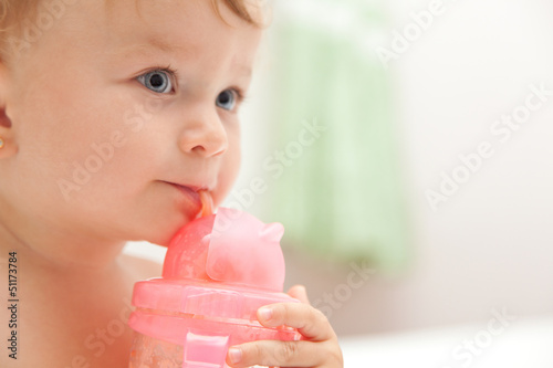 The little blue-eyed baby girl drinks juice from a bottle
