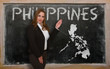 Teacher showing map of philippines on blackboard