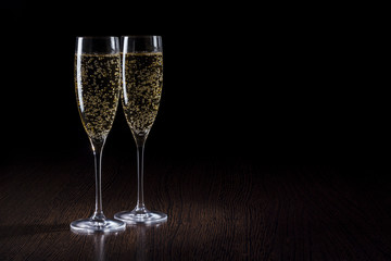 Champagne into glass on a black and wooden table