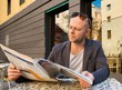 MIddle-aged man reading newspaper behind table in street cafe