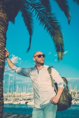 Middle-aged man with backpack standing near palm tree against ya