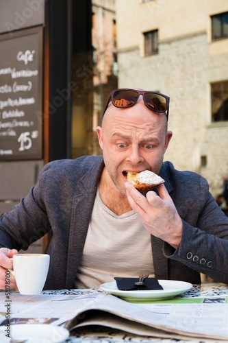 Surprised middle-aged man reading newspaper