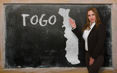 Teacher showing map of togo on blackboard