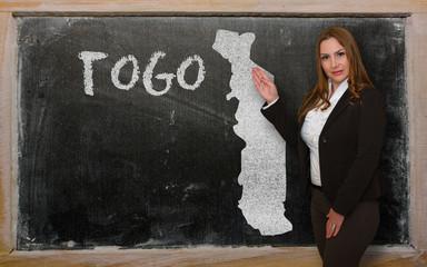 Teacher showing map of togo on blackboard