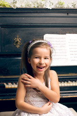 girl in a beautiful dress near the piano happy