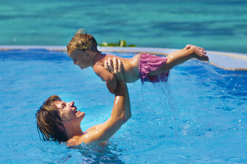 young happy mother and baby enjoying vacation in swimming pool o