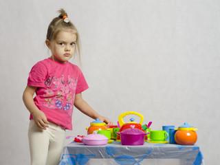 Девочка играет детской кухонной посудой