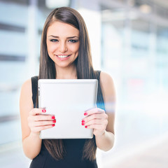 Businesswoman in front of office building holding tablet