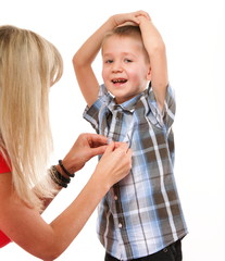 Mother fixing young boy's shirt